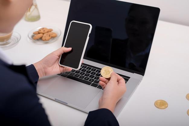 Junge kaukasische frau, die bitcoin auf dem schreibtisch hält und auf dem smartphone tippt