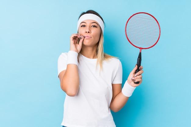 Junge kaukasische frau, die das badminton lokalisiert mit den fingern auf den lippen halten ein geheimnis spielt.