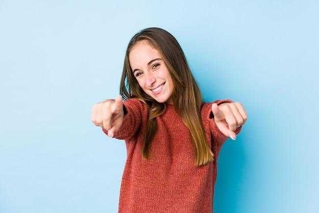 Junge kaukasische frau, die das getrennte freundliche lächeln zeigt auf frontseite aufwirft.