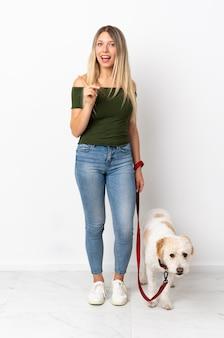 Junge kaukasische frau, die den hund auf weiß zeigt zur seite zeigt, um ein produkt zu präsentieren