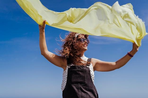 Junge kaukasische frau, die draußen mit gelbem schal an einem windigen und sonnigen tag spielt. lebensstil und sommerzeit