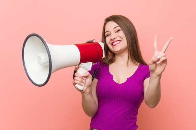 Junge kaukasische frau, die durch ein megaphon spricht