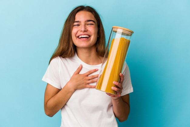 Junge kaukasische frau, die ein auf blauem hintergrund isoliertes pastaglas hält, lacht laut und hält die hand auf der brust.