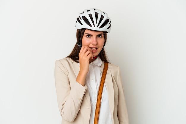 Junge kaukasische frau, die ein fahrrad reitet, um auf weißem hintergrund zu arbeiten, der fingernägel beißt, nervös und sehr ängstlich.