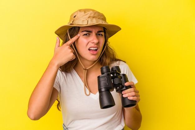 Junge kaukasische frau, die ein fernglas auf gelbem hintergrund hält, das eine enttäuschungsgeste mit dem zeigefinger zeigt.