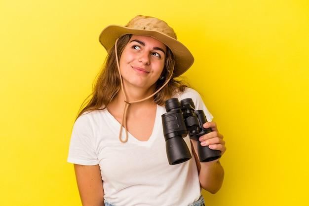 Junge kaukasische frau, die ein fernglas auf gelbem hintergrund hält und davon träumt, ziele und zwecke zu erreichen