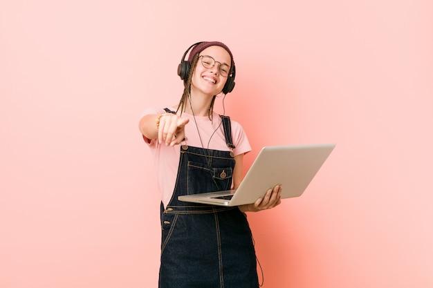 Junge kaukasische frau, die ein freundliches lächeln des laptops zeigt auf front hält.