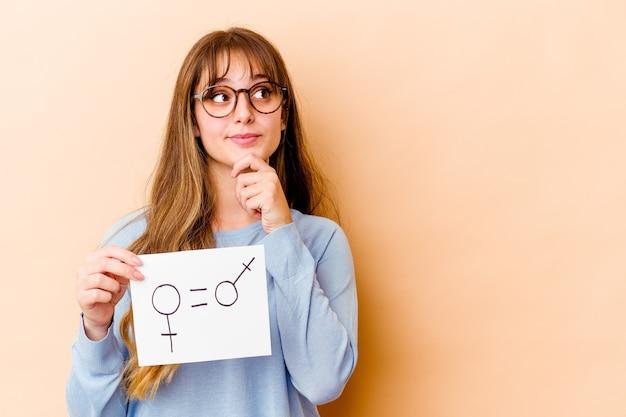 Junge kaukasische frau, die ein gleichheitsgeschlechtsplakat hält, das seitlich mit zweifelhaftem und skeptischem ausdruck schaut.