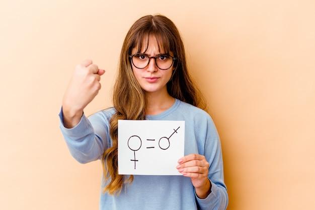Junge kaukasische frau, die ein gleichstellungs-gender-plakat hält, isoliert mit faust zur kamera, aggressiver gesichtsausdruck.
