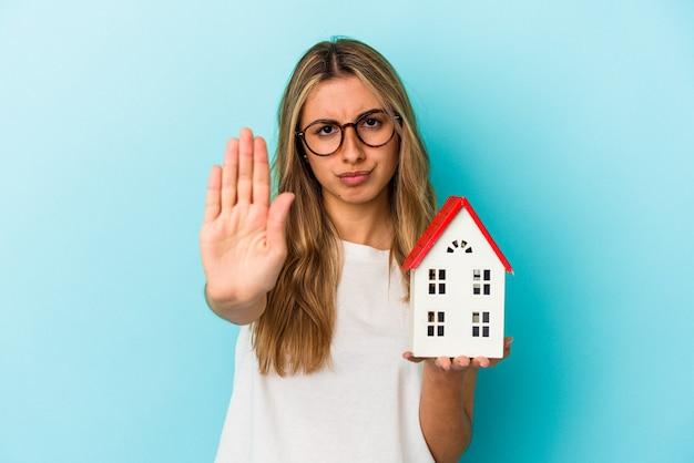 Junge kaukasische frau, die ein hausmodell lokalisiert auf blauem hintergrund steht, das mit ausgestreckter hand steht, die stoppschild zeigt, das sie verhindert.