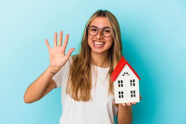 Junge kaukasische frau, die ein hausmodell lokalisiert auf der blauen wand hält, die fröhlich zeigt nummer fünf mit den fingern zeigt