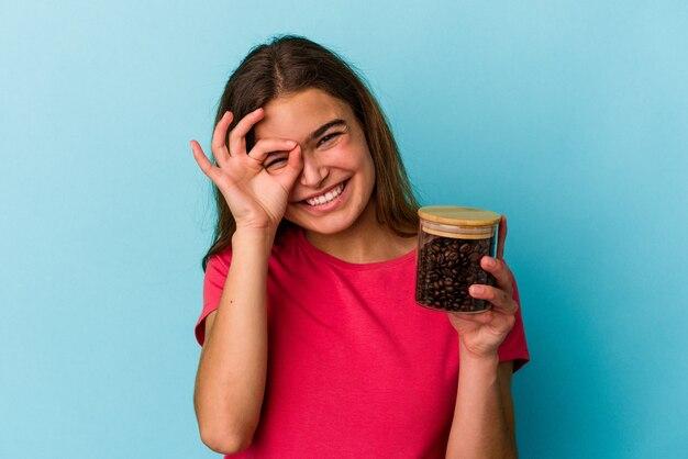 Junge kaukasische frau, die ein kaffeeglas auf blauem hintergrund isoliert hält, aufgeregt, die geste auf dem auge zu halten.
