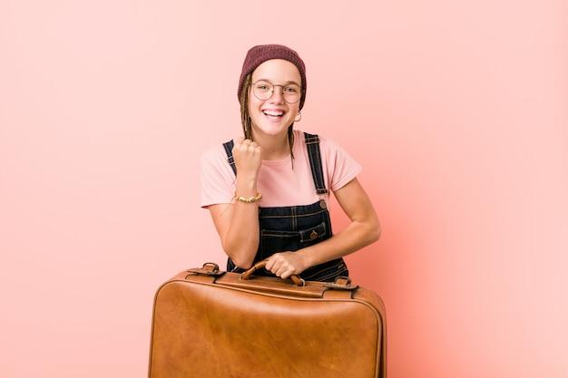 Junge kaukasische frau, die ein kofferzujubeln sorglos und aufgeregt hält. sieg-konzept.