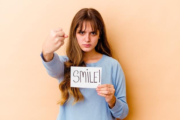 Junge kaukasische frau, die ein lächelnplakat lokalisiert hält
