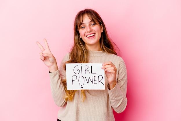Junge kaukasische frau, die ein mädchen-kraftplakat lokalisiert auf rosa wand freudig und sorglos zeigt ein friedenssymbol mit den fingern hält.