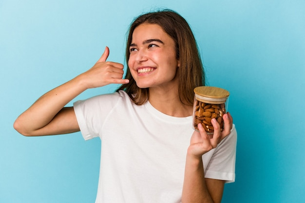 Junge kaukasische frau, die ein mandelglas auf blauem hintergrund isoliert hält und eine handy-anrufgeste mit den fingern zeigt.