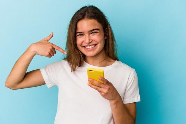 Junge kaukasische frau, die ein mobiltelefon einzeln auf blauem hintergrund hält, das mit der hand auf einen hemdkopierraum zeigt, stolz und selbstbewusst