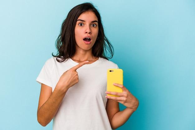 Junge kaukasische frau, die ein mobiltelefon hält, das auf blauem hintergrund isoliert zur seite zeigt