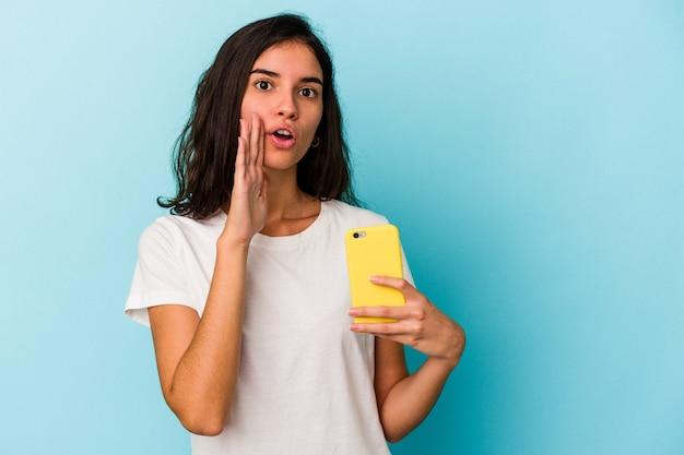 Junge kaukasische frau, die ein mobiltelefon isoliert auf blauem hintergrund hält, sagt eine geheime heiße bremsnachricht und schaut beiseite
