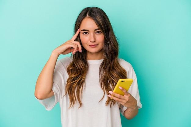 Junge kaukasische frau, die ein mobiltelefon isoliert auf blauem hintergrund hält und mit dem finger auf den tempel zeigt, denkt, konzentriert sich auf eine aufgabe.