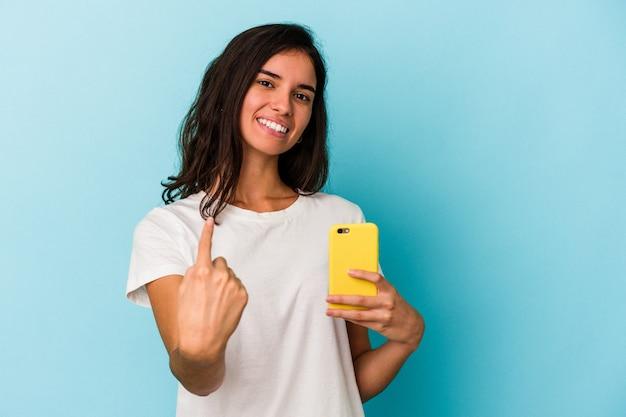 Junge kaukasische frau, die ein mobiltelefon isoliert auf blauem hintergrund hält und mit dem finger auf sie zeigt, als ob sie einladen würde, näher zu kommen.