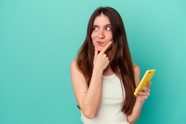 Junge kaukasische frau, die ein mobiltelefon isoliert auf blauer wand hält und seitlich mit zweifelhaftem und skeptischem ausdruck schaut.
