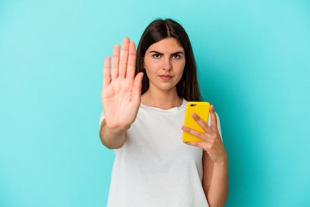 Junge kaukasische frau, die ein mobiltelefon lokalisiert auf der blauen wand hält, die mit ausgestreckter hand steht, die stoppschild zeigt, das sie verhindert