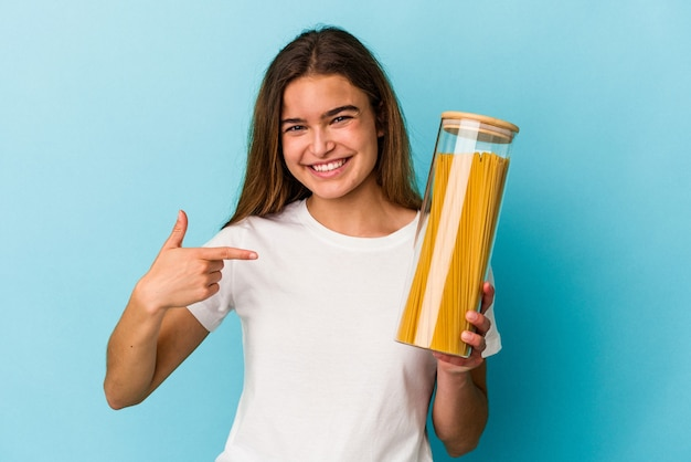 Junge kaukasische frau, die ein nudelglas hält, isoliert auf blauem hintergrund, die mit der hand auf einen hemdkopierraum zeigt, stolz und selbstbewusst