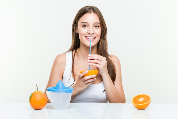 Junge kaukasische frau, die ein orange withstraw trinkt. gesundes leben