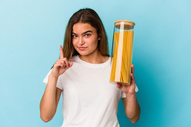 Junge kaukasische frau, die ein pastaglas auf blauem hintergrund isoliert hält und nummer eins mit dem finger zeigt.