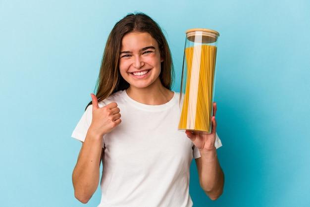 Junge kaukasische frau, die ein pastaglas hält, isoliert auf blauem hintergrund, lächelt und hebt den daumen hoch