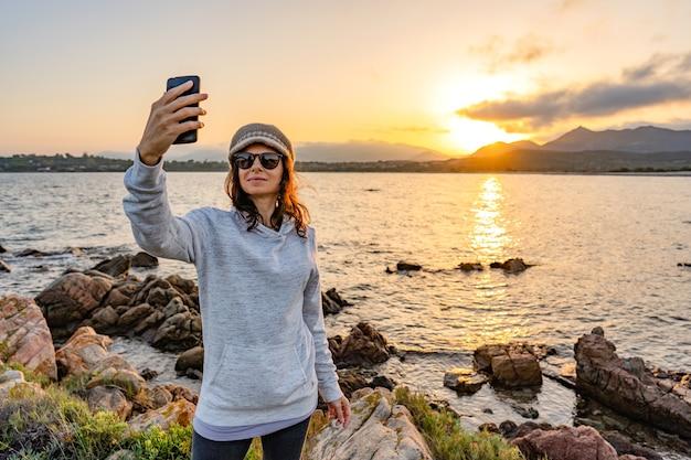 Junge kaukasische frau, die ein selbstporträt mit sonnenbrille und wollhut auf ozeansee-resort bei sonnenuntergang oder morgengrauen nimmt. alleinreisender, der spaß hat, ihr foto auf sozialem netzwerk zu teilen