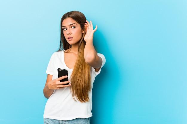 Junge kaukasische frau, die ein telefon hält, das versucht, einen klatsch zu hören.