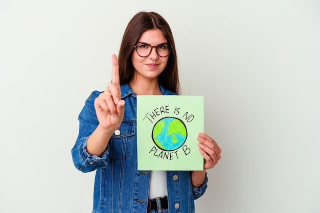 Junge kaukasische frau, die ein veganes lebensplakat lokalisiert auf weißen wandabdeckungsohren mit händen hält