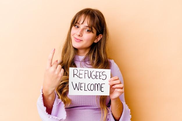 Junge kaukasische frau, die ein willkommensplakat für flüchtlinge hält, das isoliert mit dem finger auf sie zeigt, als ob sie einladen würde, näher zu kommen.