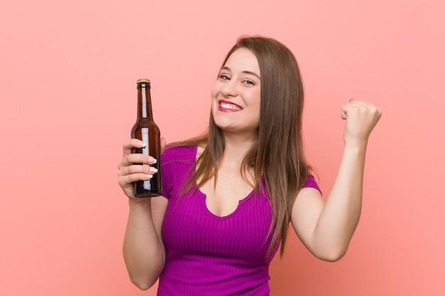 Junge kaukasische frau, die eine bierflasche anhält