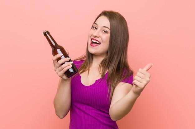 Junge kaukasische frau, die eine bierflasche hält