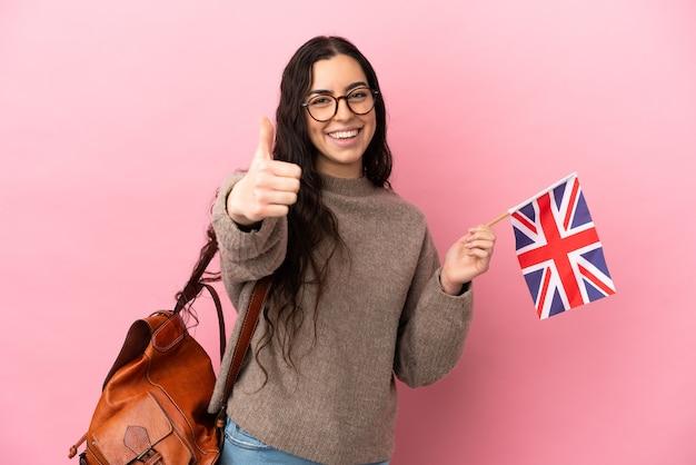 Junge kaukasische frau, die eine britische flagge hält, die auf rosa wand mit daumen oben lokalisiert wird, weil etwas gutes passiert ist