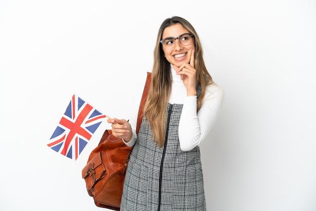 Junge kaukasische frau, die eine britische flagge isoliert auf weißem hintergrund hält und beim nachschlagen eine idee denkt