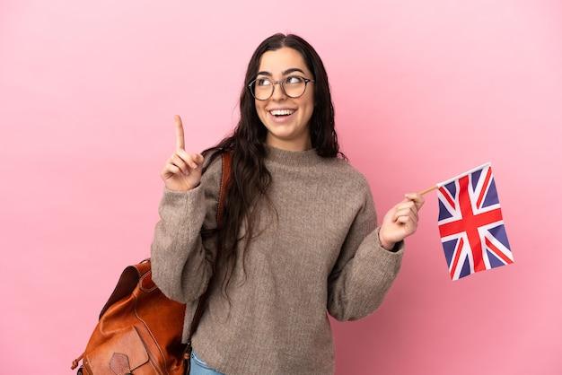 Junge kaukasische frau, die eine britische flagge lokalisiert auf rosa hintergrund hält, der eine große idee aufzeigt