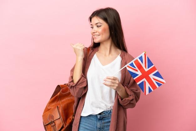 Junge kaukasische frau, die eine flagge des vereinigten königreichs hält, die isoliert auf die seite zeigt, um ein produkt zu präsentieren?