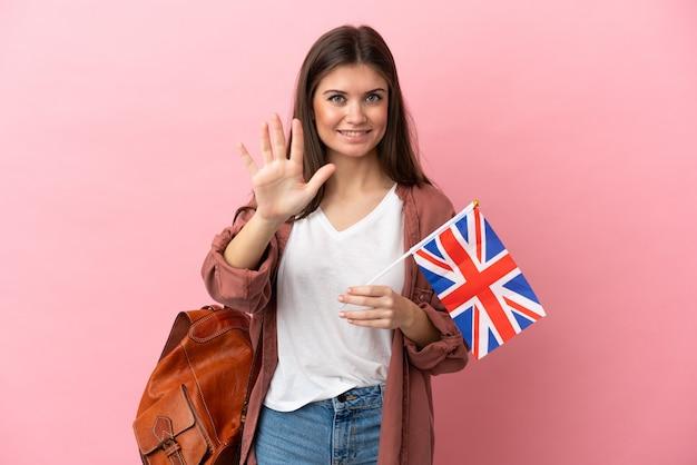 Junge kaukasische frau, die eine flagge des vereinigten königreichs hält, die isoliert fünf mit den fingern zählt
