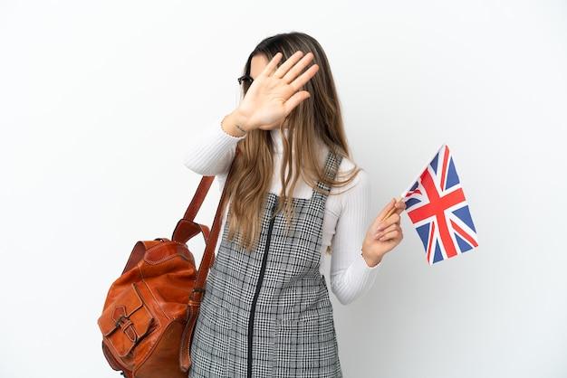 Junge kaukasische frau, die eine flagge des vereinigten königreichs lokalisiert auf weißem hintergrund hält, die stoppgeste macht und enttäuscht