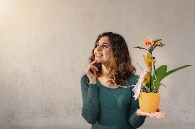 Junge kaukasische frau, die eine gelbe orchideenpflanze hält. mit nachdenklichem lächeln nach oben schauen.