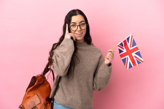 Junge kaukasische frau, die eine großbritannienflagge lokalisiert auf rosa hintergrund hält, der eine idee denkt