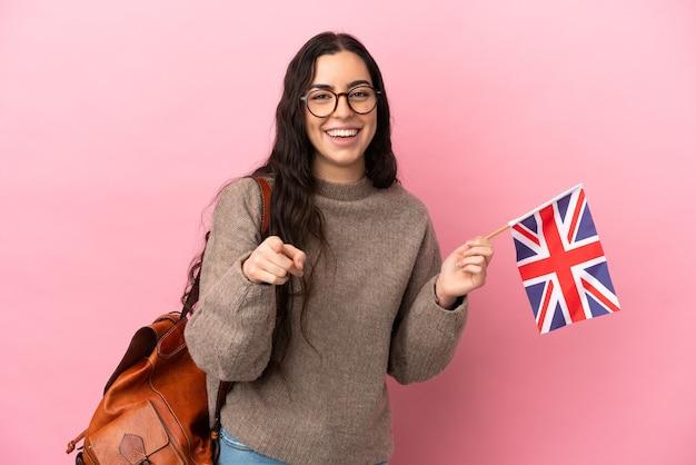 Junge kaukasische frau, die eine großbritannienflagge lokalisiert auf rosa hintergrund überrascht und nach vorne zeigend hält