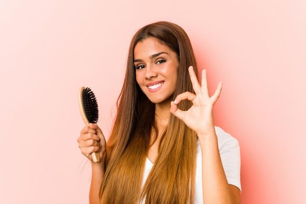 Junge kaukasische frau, die eine haarbürste nett und überzeugt hält, okaygeste zeigend.