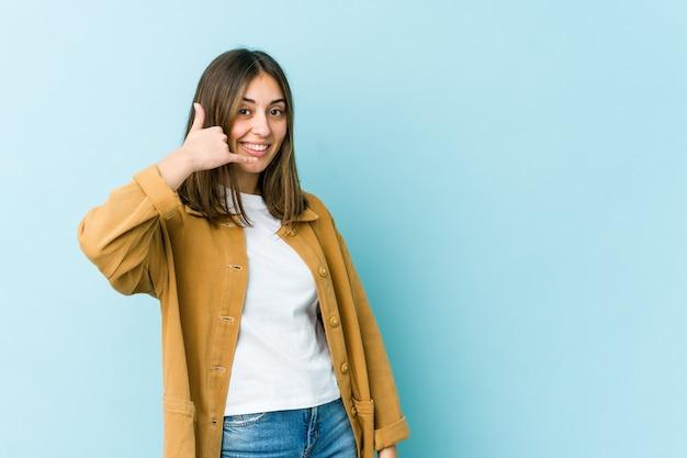 Junge kaukasische frau, die eine handy-anrufgeste mit den fingern zeigt.