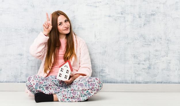 Junge kaukasische frau, die eine hausikone hält, die siegeszeichen zeigt und breit lächelt.