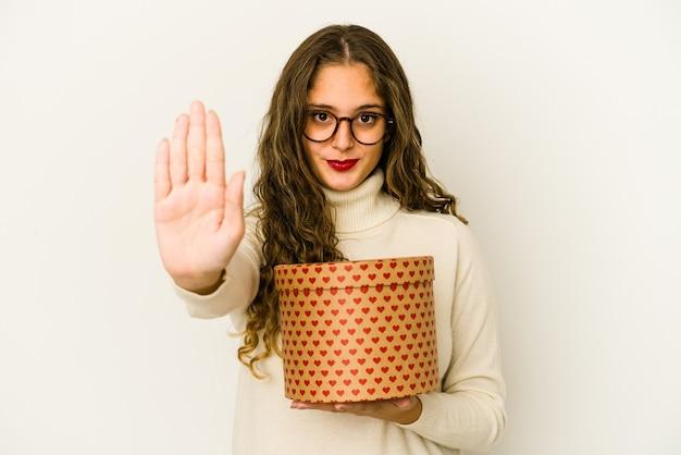 Junge kaukasische frau, die eine herz-valentinsgruß-tagesbox lokalisiert steht, die mit ausgestreckter hand steht, die stoppschild zeigt, sie verhindern.